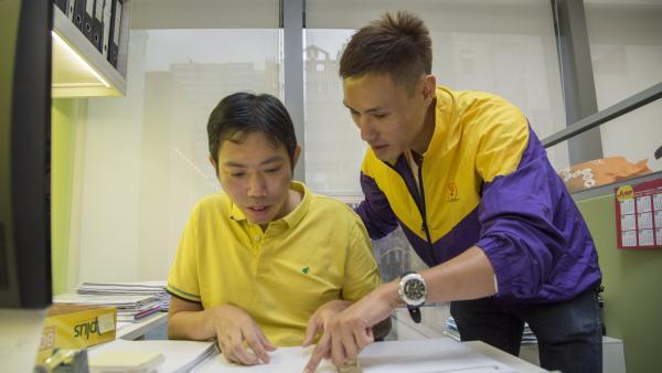 職業治療師正為工作中的學員進行實地工作指導。